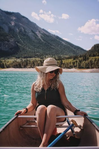 Woman sitting on boat in lake against mountains