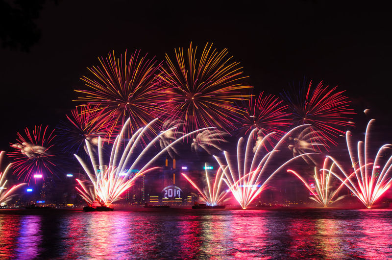Low angle view of firework display over river at night