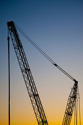 Crainspotting. Sky Machinery Sunset Crane - Construction Machinery Industry Construction Industry Development Construction Site Silhouette Metal Clear Sky Construction Machinery No People Blue Orange Color Tall - High