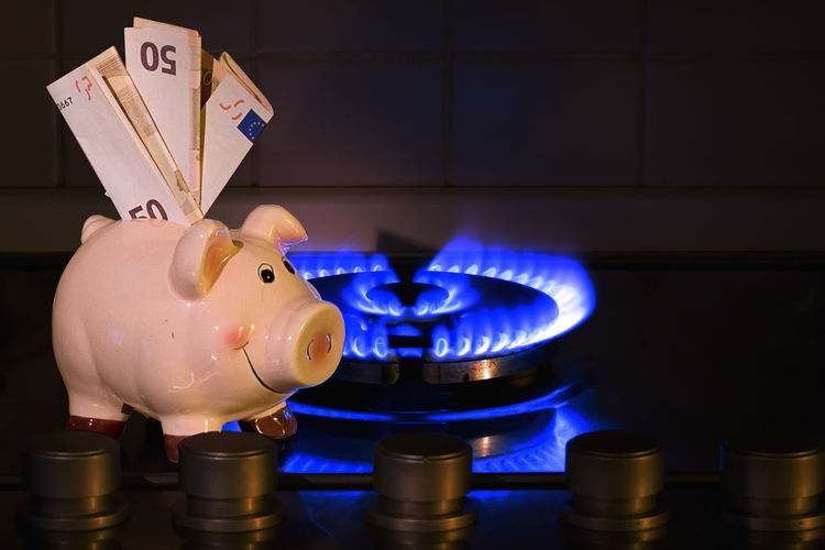 Close-up of piggy bank with paper currency by illuminated burner in kitchen at home