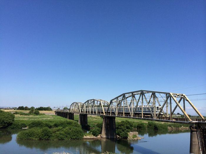Train On Railroad Bridge Against Clear Sky