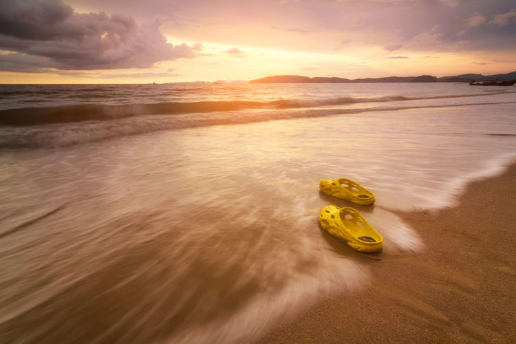 Yellow shoes on the beach and Sunset Sky Water Sunset Cloud - Sky Sea Beauty In Nature Scenics - Nature Beach Horizon Over Water Land Nature Tranquility Orange Color Horizon Tranquil Scene Motion Transportation Idyllic No People Outdoors