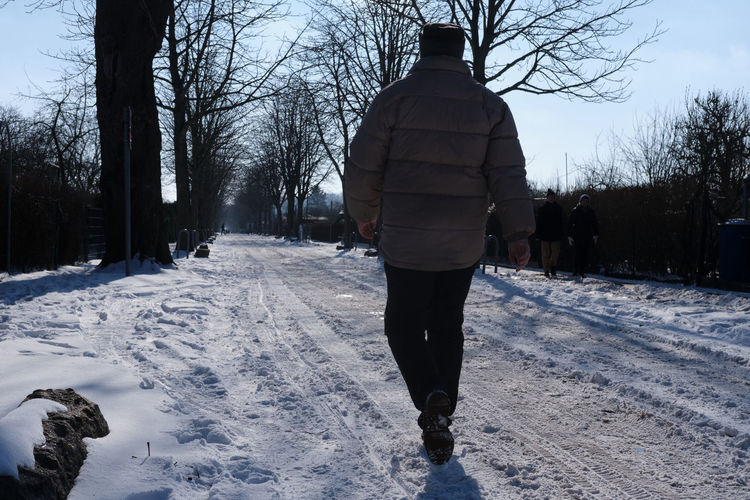 Rear view of man walking on snow covered footpath