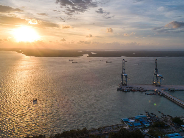 Heavy duty crane at port area during sunset Water Sky Sunset Sea Cloud - Sky Transportation Scenics - Nature Nautical Vessel Beauty In Nature Nature Architecture No People Horizon Mode Of Transportation Built Structure Horizon Over Water Orange Color Sun High Angle View Luxury