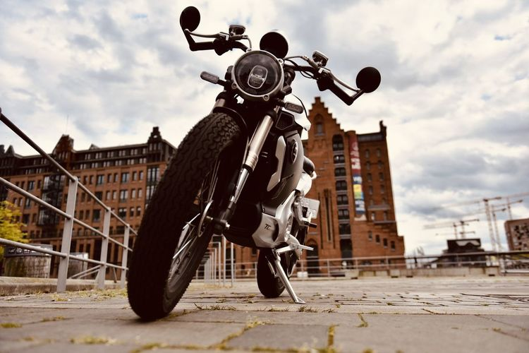 Low angle view of motorcycle against building in city
