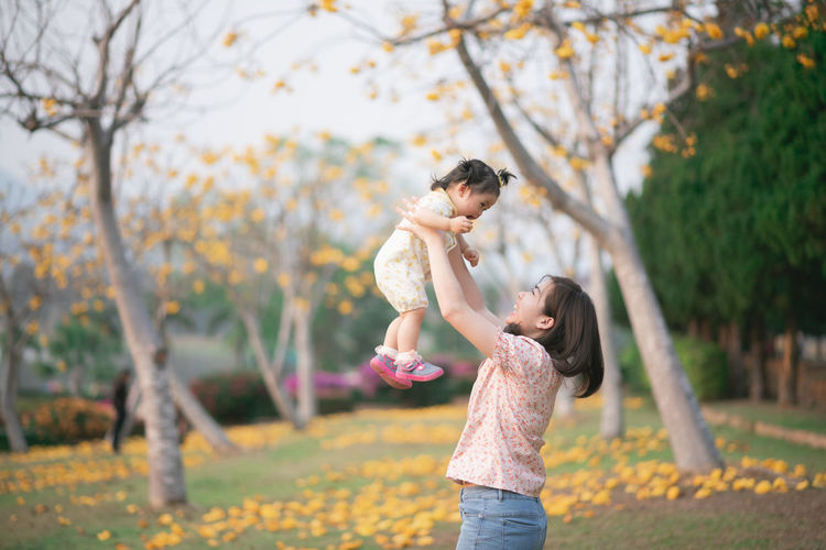 Side view of mother picking up daughter while standing in park