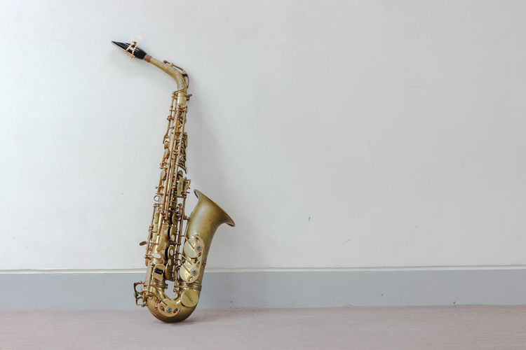 Music Instrument Alto Saxophone Wall - Building Feature Indoors  No People Music Metal Musical Instrument Still Life Flooring Copy Space Studio Shot White Background Musical Equipment Brass Instrument  Arts Culture And Entertainment Wind Instrument Home Interior Brass Hardwood Floor Wood - Material Single Object