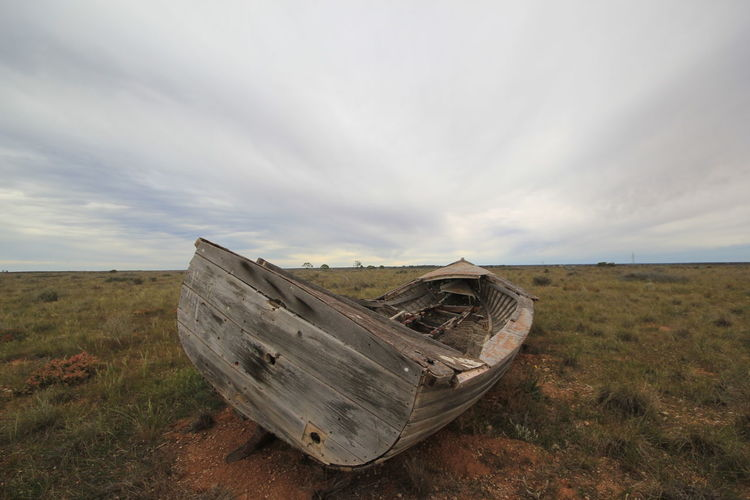Abandoned Boat On Field By Sea Against Sky