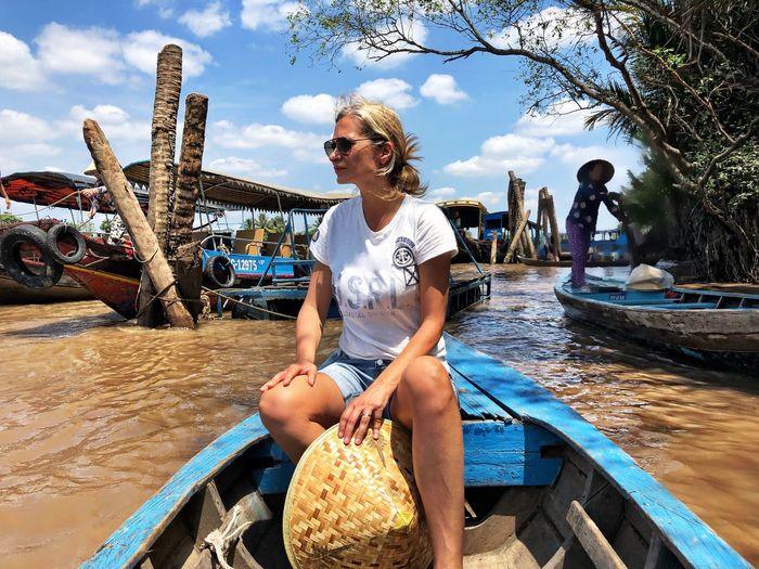 Woman looking away while sitting on rowboat in river
