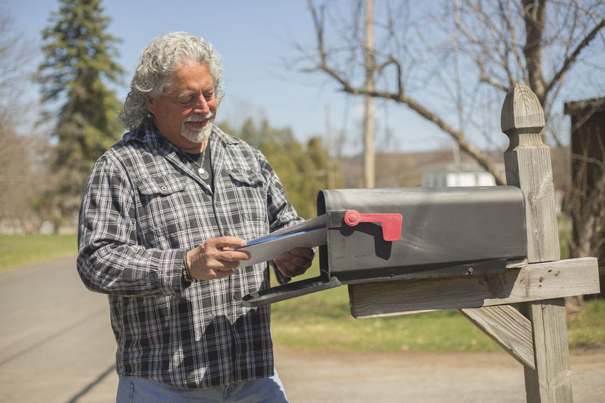 Horizontal image of older man reading mail. Communication Day Holding Leisure Activity Letters Lifestyles Mail Mailbox Nature One Person Outdoors People Real People Senior Adult Senior Men Smiling Standing Sunny Tree