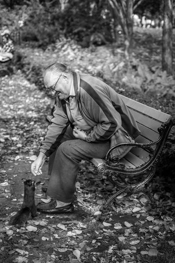 Autumn Feeding  Man Park Bench Squirrel Black And White Break Day Documentary Full Length Leaves Lunch Time Nature One Person Outdoors People Real People Senior Adult Sitting Streetphotography Tree Bnw_collection Second Acts Black And White Friday This Is Aging The Street Photographer - 2018 EyeEm Awards Autumn Mood Streetwise Photography The Art Of Street Photography