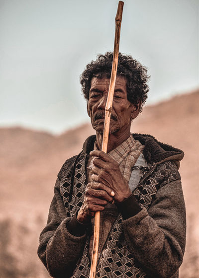 Senior man holding stick standing outdoors