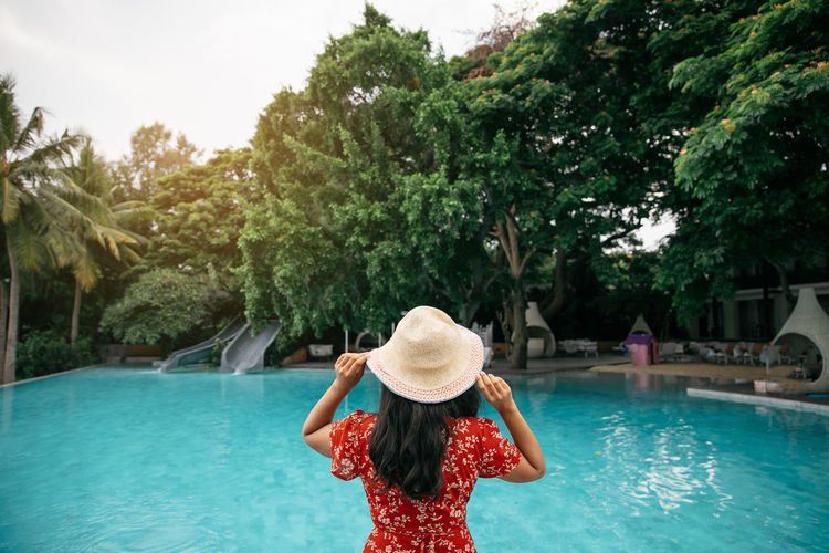 Woman relaxing in swimming pool at spa and spa relax concept in Thailand. Holiday Lifestyle Relaxing Travel Clothing Day Hairstyle Hat Human Arm Leisure Activity Lifestyles Nature One Person Outdoors Plant Pool Real People Rear View Standing Sun Hat Swimming Pool Tree Water Women Young Adult