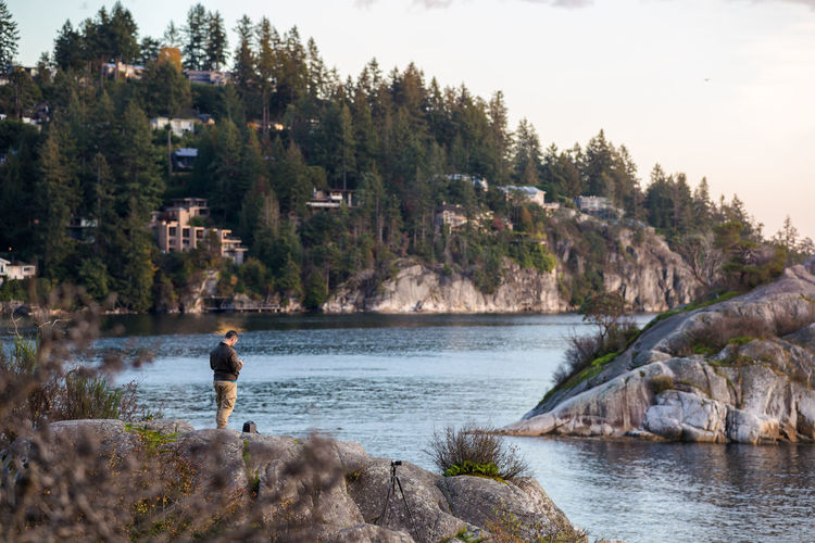 Rear view of man standing by lake