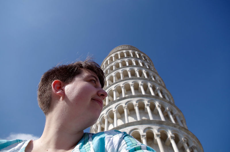 Low Angle View Of Young Woman By Tower Of Pisa