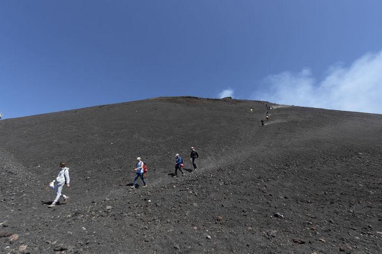 People walking on mountain road against sky