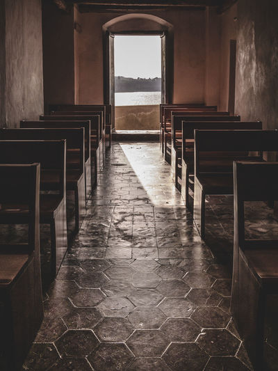 Empty pew in church with river and sky seen through window