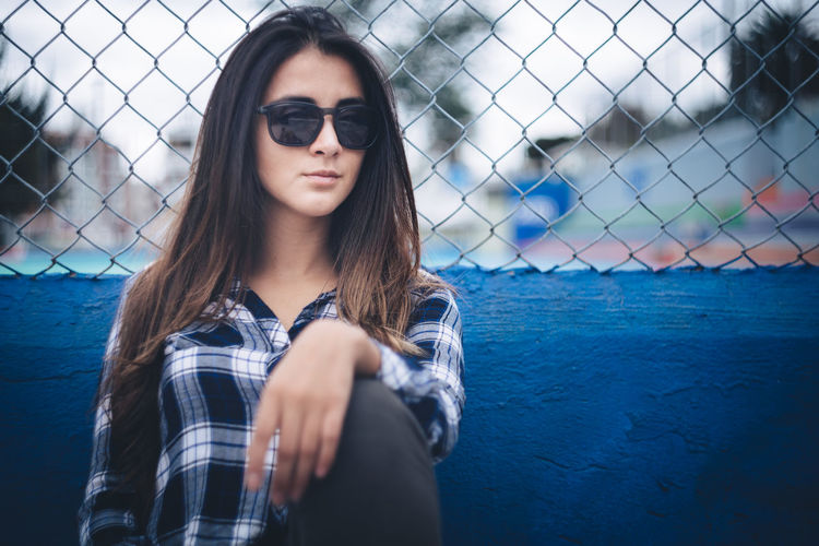 Portrait Of Beautiful Young Woman Wearing Sunglasses By Fence
