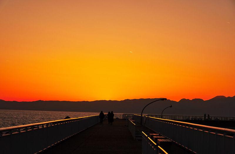 Silhouette people on sea against orange sky during sunset