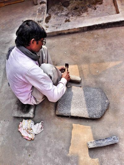 High angle view of man carving stones while sitting outdoors