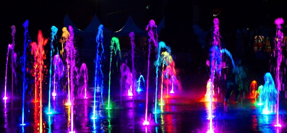 Panoramic view of colorful illuminated fountains at night