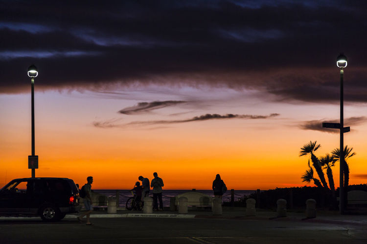 Silhouette People At Beach Against Cloudy Sky At Sunset
