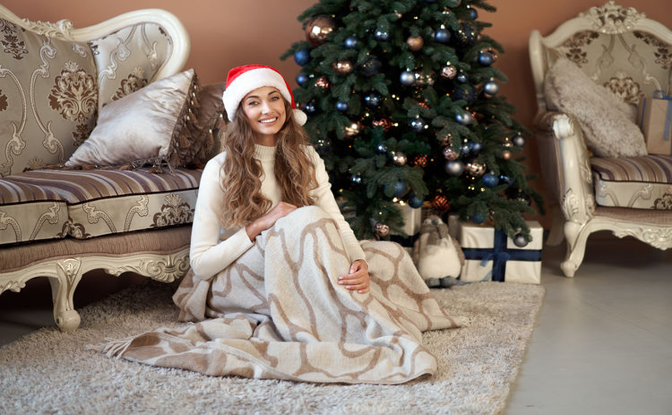 Full length of woman sitting at christmas tree at home