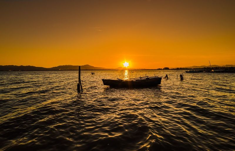 Sunset Water Sky Scenics - Nature Orange Color Nautical Vessel Transportation Beauty In Nature Mode Of Transportation Tranquility Sea Idyllic Sunlight Waterfront Reflection Tranquil Scene Silhouette Nature Outdoors