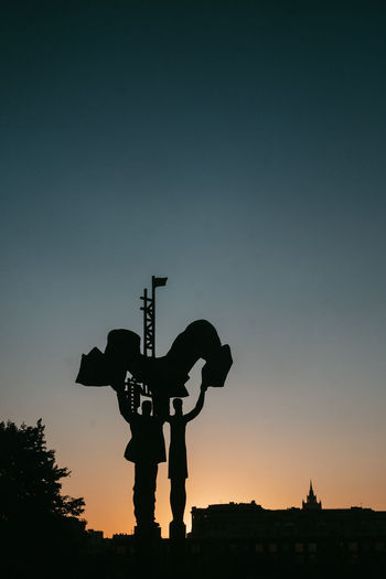 Silhouette man standing by sign against sky during sunset