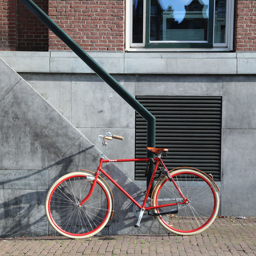 Bicycle parked on footpath against building