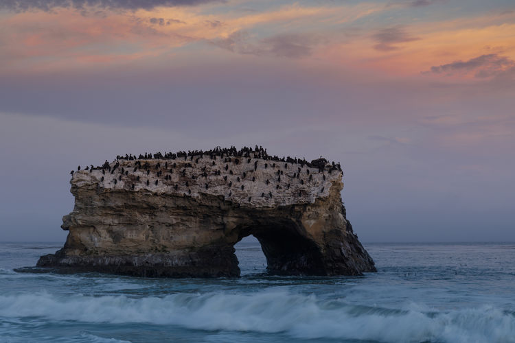 Rock formation in sea against sky at sunset