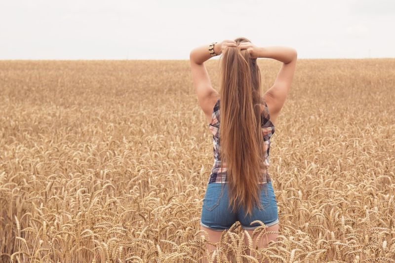 Rear view of young woman standing in farm