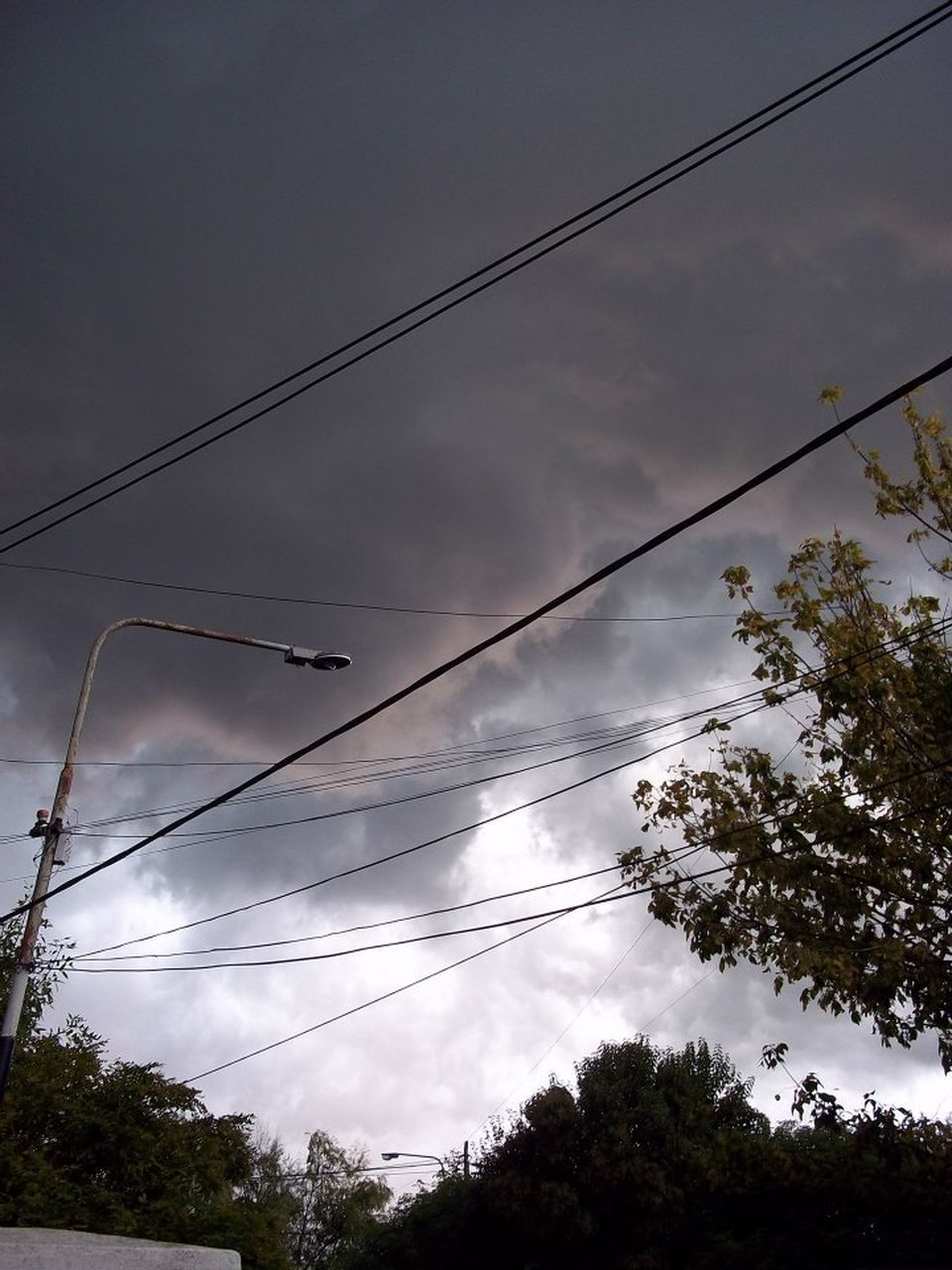 LOW ANGLE VIEW OF POWER LINE AGAINST CLOUDY SKY