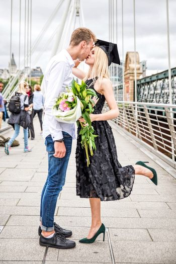 Woman Wearing Mortarboard And Holding Bouquet Kissing Boyfriend On Bridge