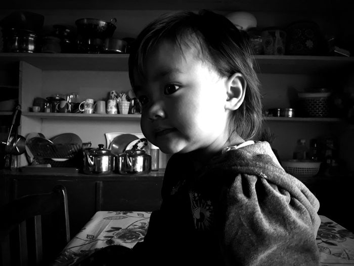 Close-up of cute girl sitting in kitchen