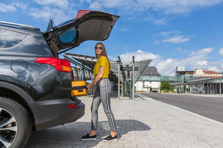 Portrait of teenage girl putting luggage in car trunk