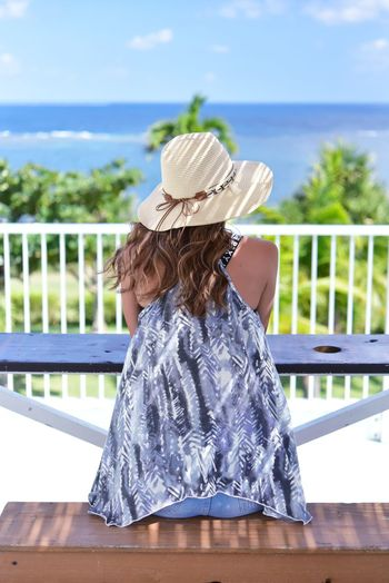 Rear view of girl wearing hat against sea