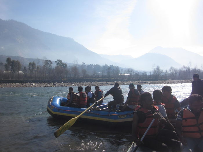 People rowing on river against sky
