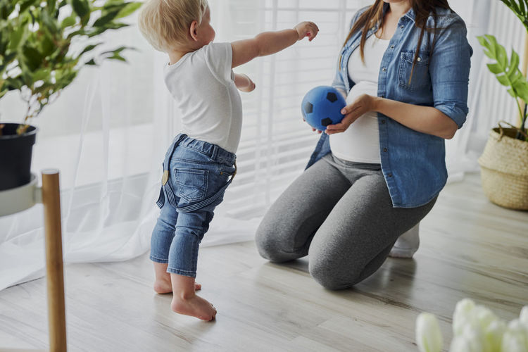 Rear view of mother and daughter on floor