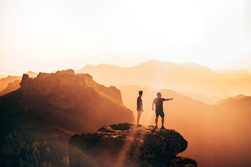 People standing on cliff against sky during sunset