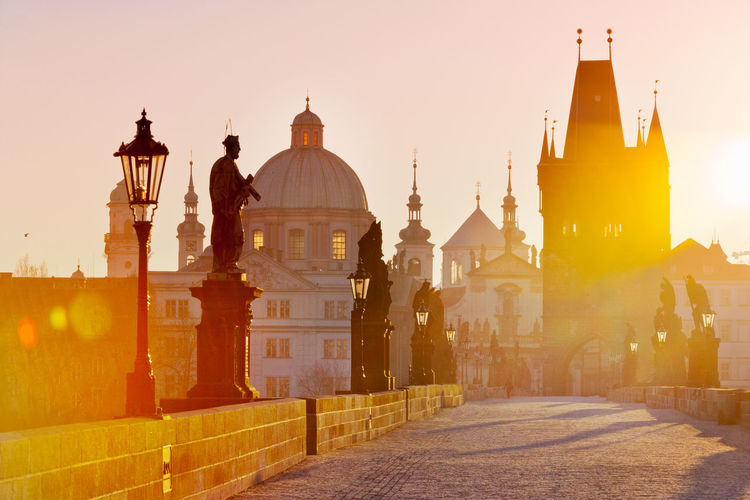 View of charles bridge with church during sunrise