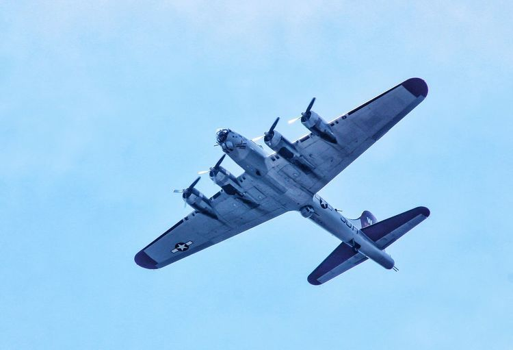 Low angle view of bomber plane against blue sky