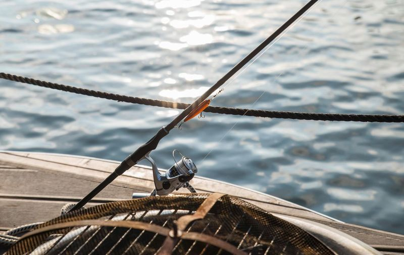 High angle view of fishing rod in boat against sea