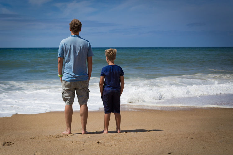 Looking out over the sea. Adult Back Beach Bonding Boys Casual Clothing Child Family Full Length Happiness Horizon Over Water Human Back Human Body Part Leisure Activity Love Males  Outdoors Rear View Relaxation Sand Sea Summer Togetherness Two People Vacations