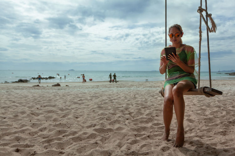 Full length of woman using digital tablet while sitting on swing at beach against sky