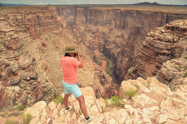 Tourist Taking Picture Of Canyon
