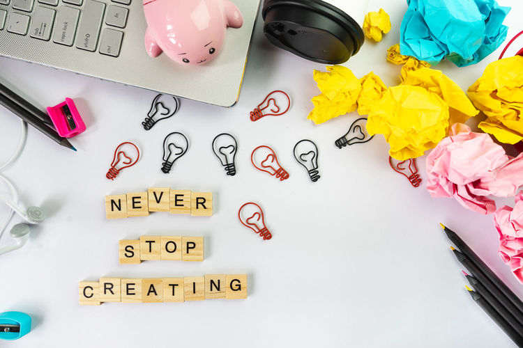 Never stop creating word on wooden block, creative idea concept with light bulb and paper crumbled paper ball Art And Craft Backgrounds Brainstorm Close-up Communication Craft Creative Creativity Crumbled Paper Ball Crumpled Paper High Angle View Indoors  Large Group Of Objects Multi Colored Never Stop Creating No People Number Paper Pen Pink Color Still Life Table Text Thiniking Variation Western Script Yellow