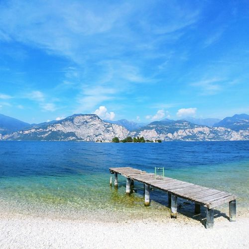 Scenic view of sea against blue sky / lake garda view / shades of blue / turquoise colour