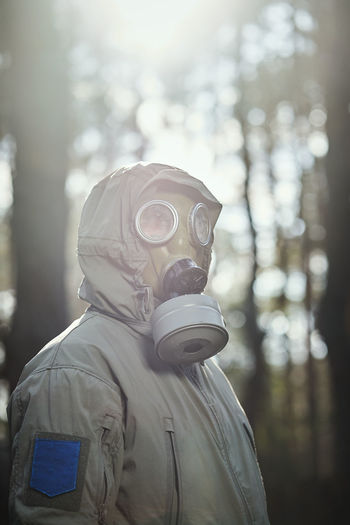 Close-up of man wearing protective suit against trees in forest