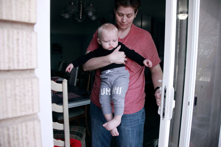 Mother carrying son while walking at doorway
